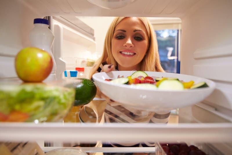 Donna che sembra frigorifero interno in pieno di alimento e che sceglie insalata fotografia stock