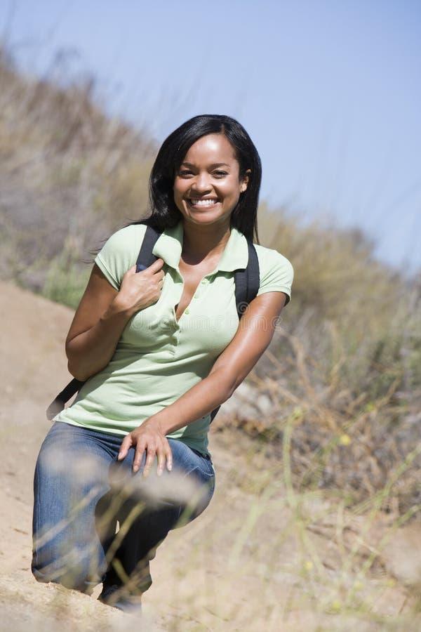 Donna che si accovaccia sul sorridere del percorso della spiaggia immagini stock