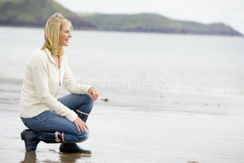 Donna che si accovaccia sulla spiaggia fotografie stock libere da diritti