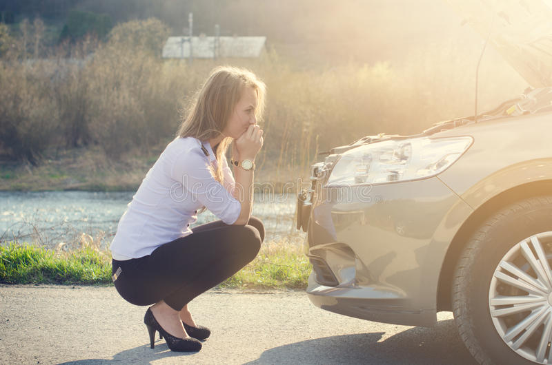 Donna che si accovaccia sulla strada accanto ad un'automobile Persona triste Automobile nociva Sfondo naturale Incidente stradale immagini stock