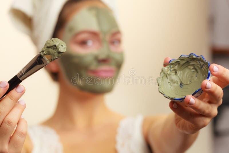 Donna che si applica con la maschera del fango dell'argilla della spazzola al suo fronte immagine stock libera da diritti