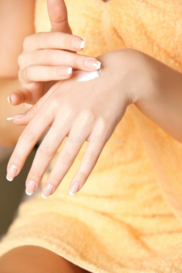 Donna che si applica la crema della pelle alle mani fotografia stock