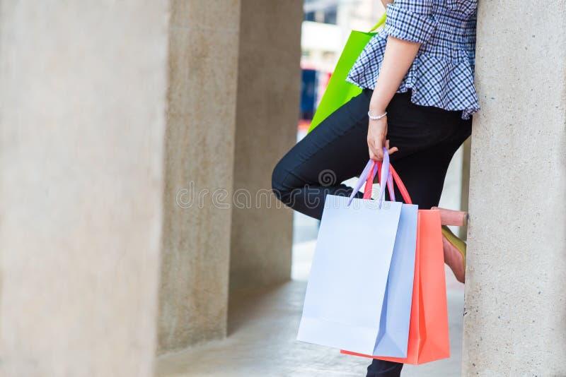 Donna che si appoggia la parete con un vantaggio che riposa sulla parete e che tiene i sacchetti della spesa variopinti, dopo il  immagine stock