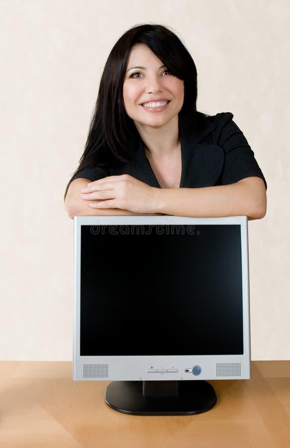 Donna che si appoggia sullo schermo dell'affissione a cristalli liquidi fotografia stock libera da diritti