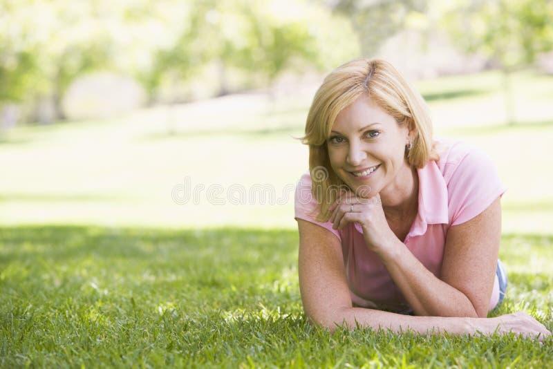 Donna che si distende all'aperto sorridere immagine stock libera da diritti