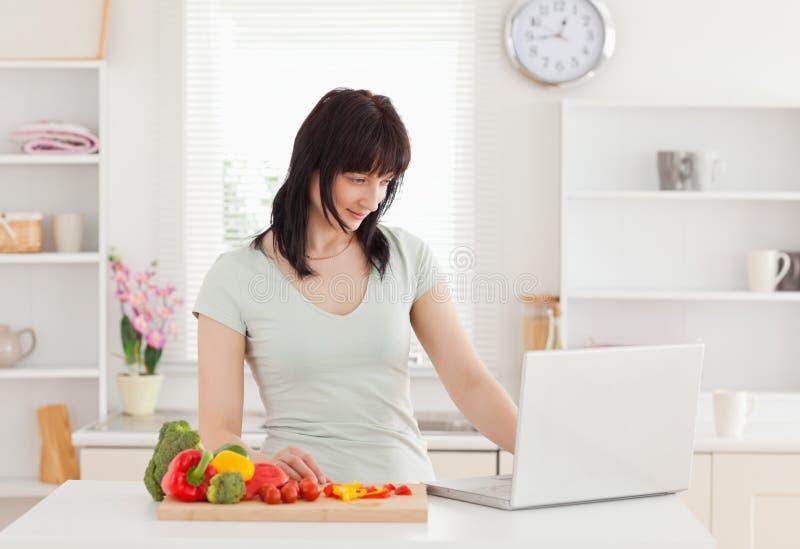 Donna che si distende con il suo computer portatile nella cucina fotografie stock