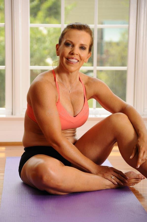 Donna che si distende dopo l'allenamento di yoga fotografia stock libera da diritti
