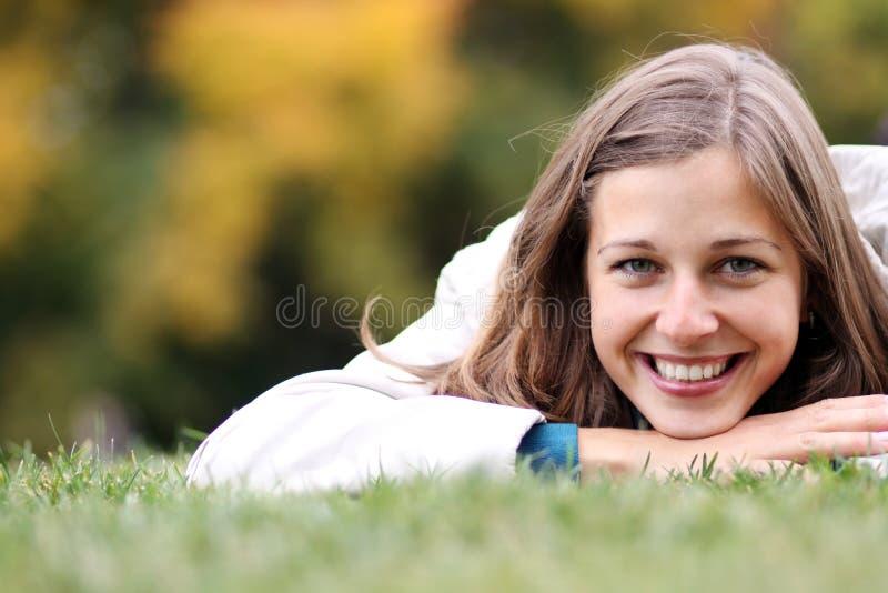 Donna che si distende nell'erba immagini stock libere da diritti