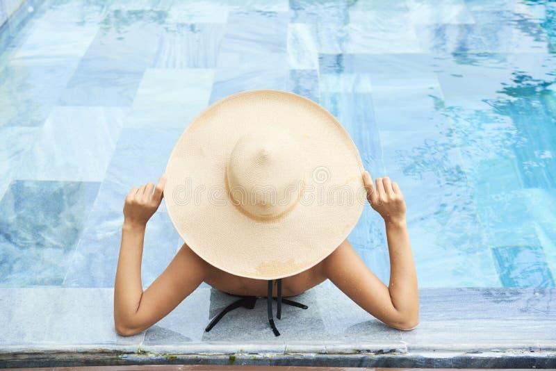 Donna che si distende nella piscina immagini stock