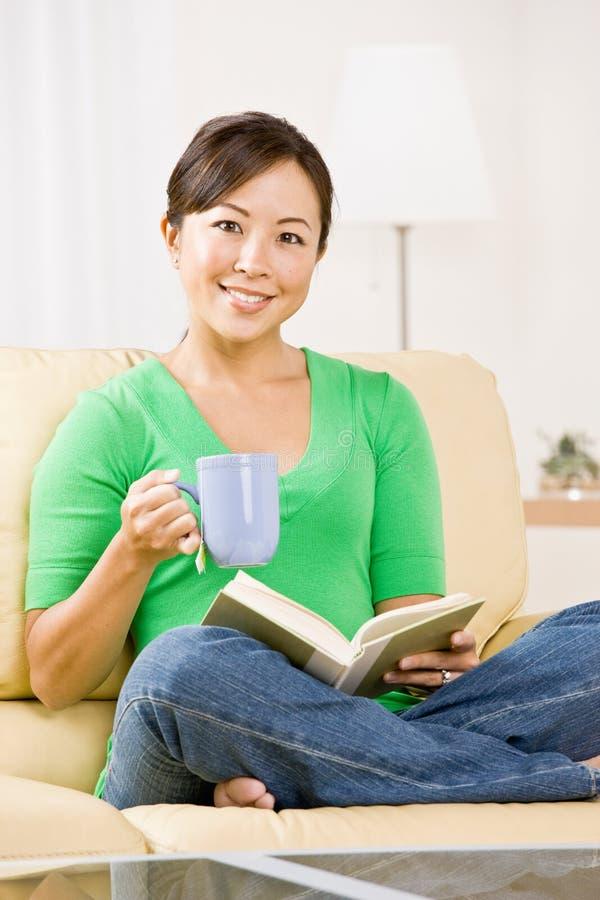 Donna che si distende sul sofà   fotografia stock