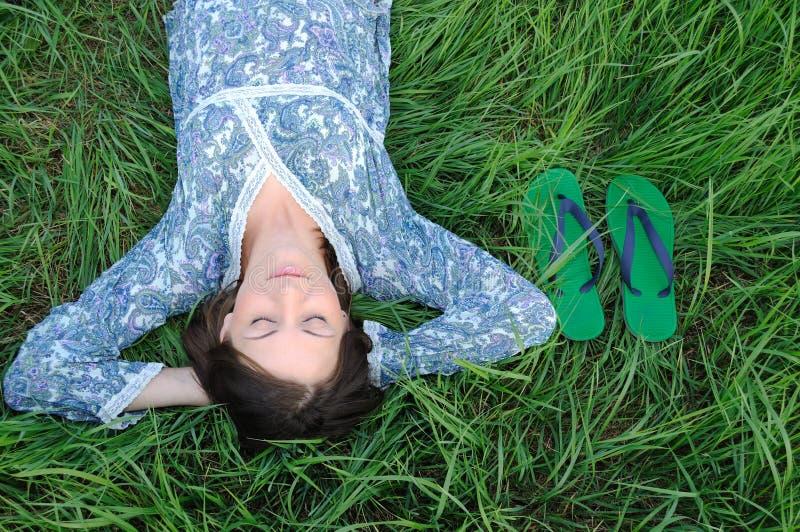 Donna che si distende sull'erba fotografia stock