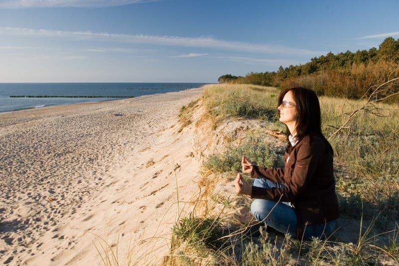 Donna che si distende sulla spiaggia immagine stock
