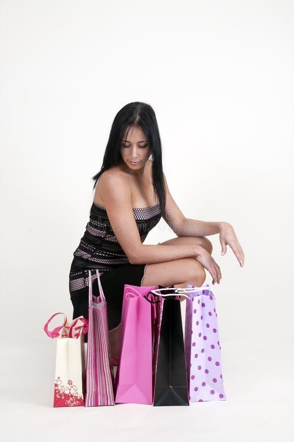 Donna che si inginocchia con i sacchetti di acquisto fotografie stock libere da diritti