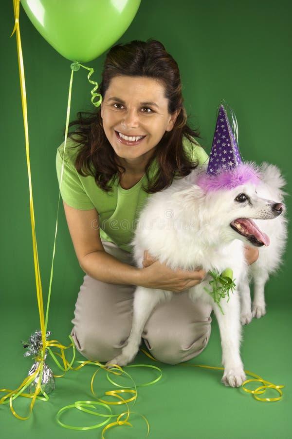 Donna che si inginocchia con il cane bianco. immagini stock