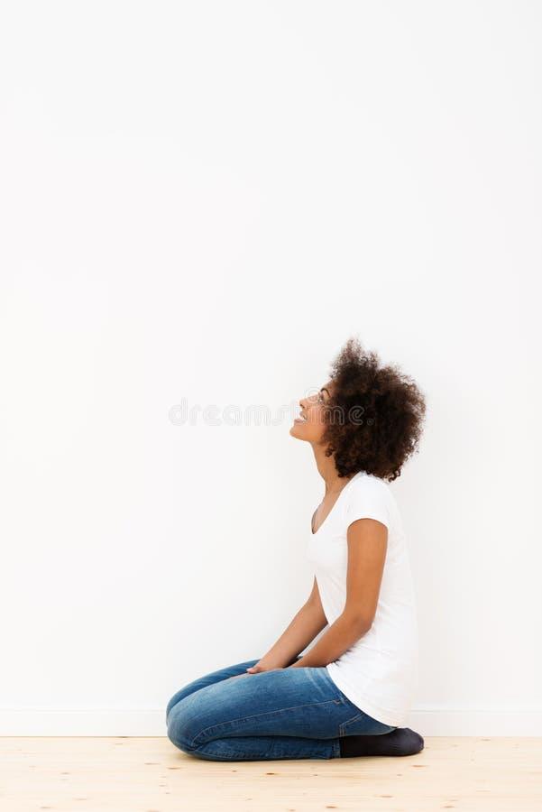 Donna che si inginocchia esaminando una parete bianca immagini stock libere da diritti