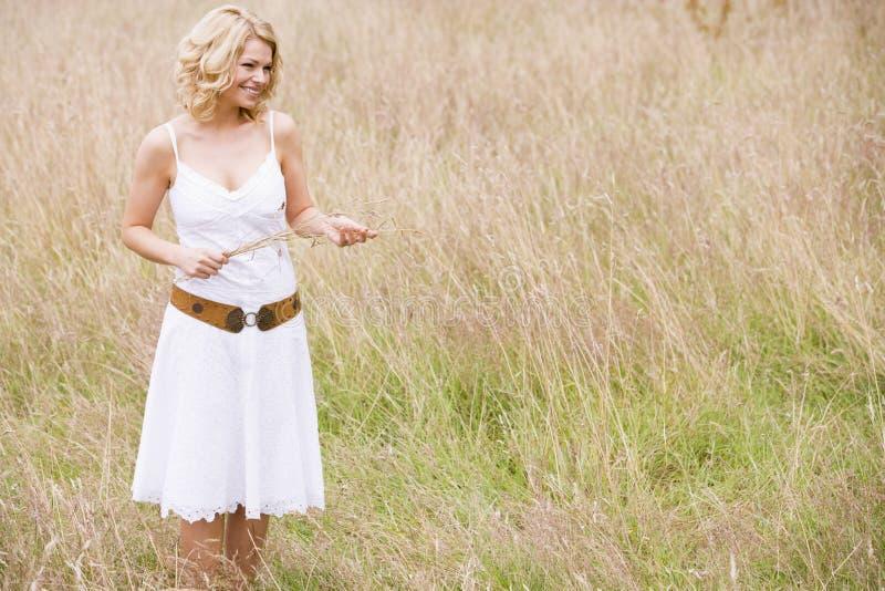 Donna che si leva in piedi all'aperto tenente sorridere dell'erba immagine stock