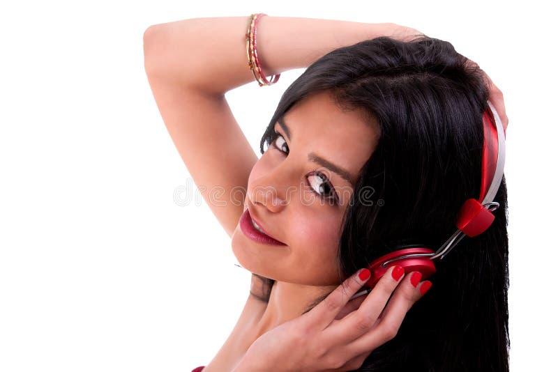 Donna che si leva in piedi ascoltante la musica sulla cuffia rossa immagini stock libere da diritti