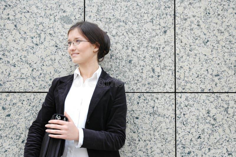 Donna che si leva in piedi davanti alla parete delle mattonelle immagini stock