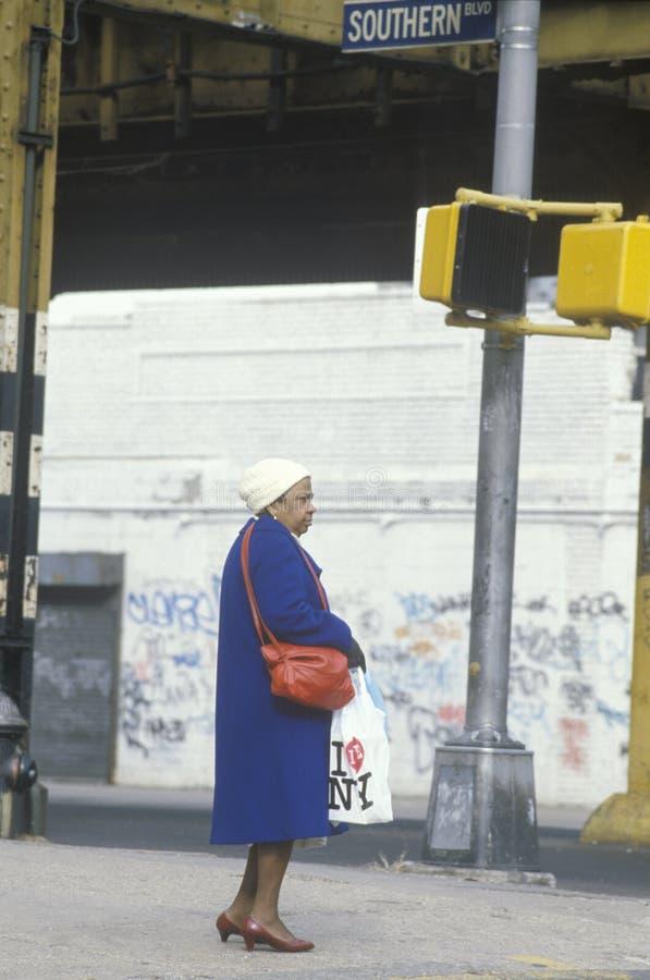 Donna che si leva in piedi sull'angolo in quartiere povero immagine stock
