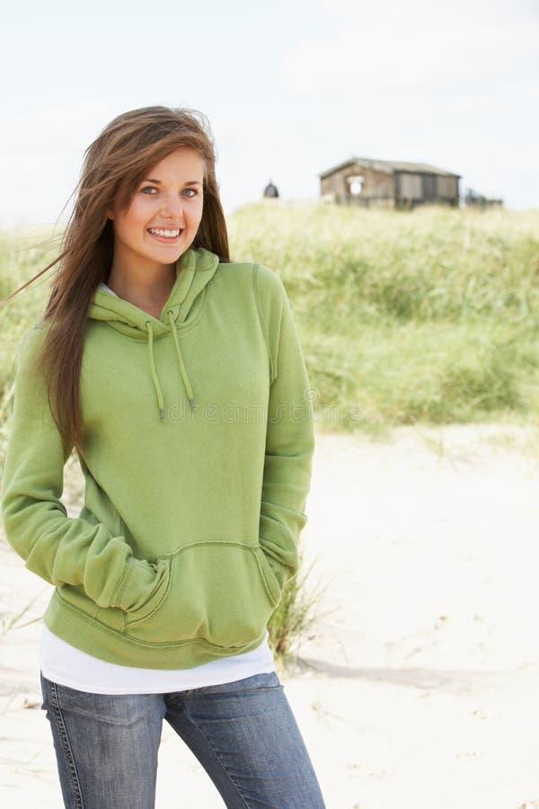 Donna che si leva in piedi sulla spiaggia che porta parte superiore incappucciata immagine stock