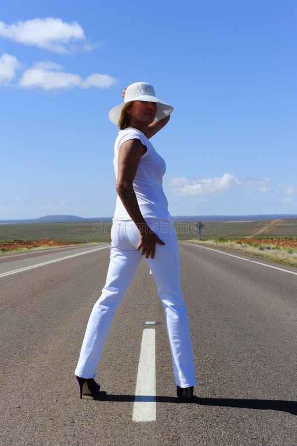 Donna che si leva in piedi sulla strada principale fotografia stock libera da diritti