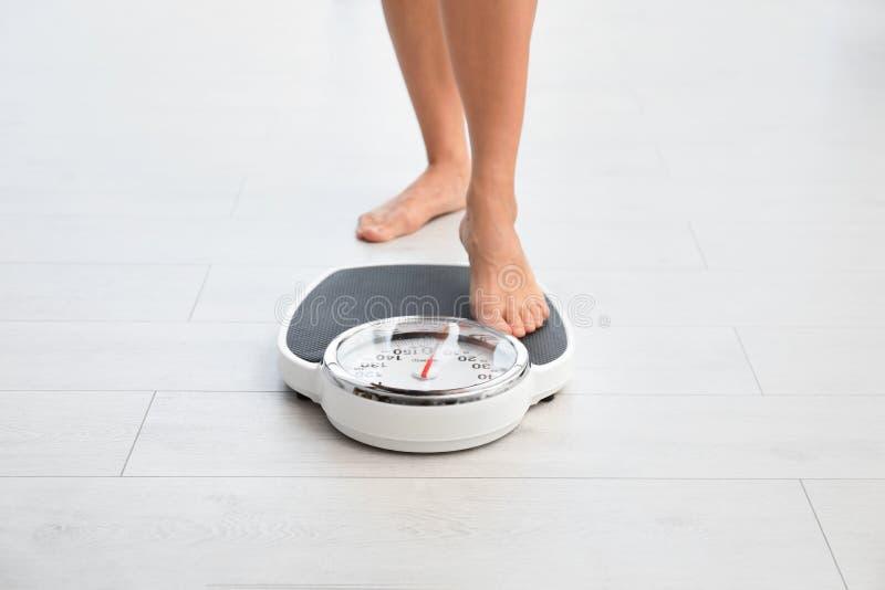 Donna che si leva in piedi sulle scale Problema di peso eccessivo fotografia stock