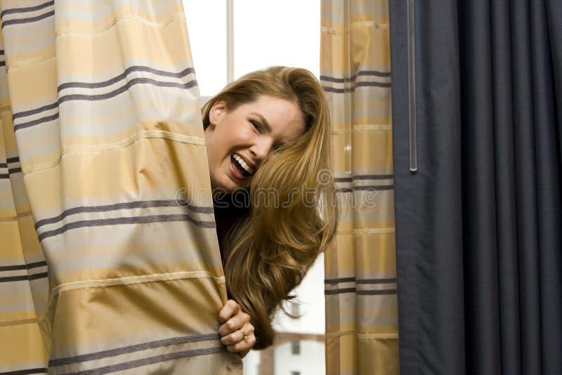Donna che si nasconde dietro le tende fotografia stock libera da diritti