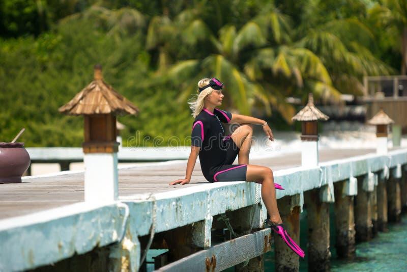 Donna che si rilassa al molo della spiaggia immagini stock libere da diritti