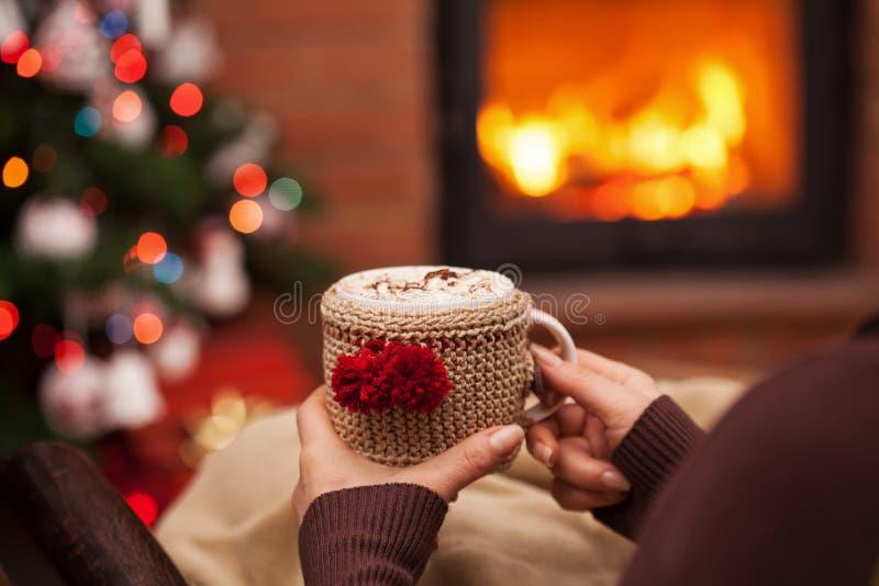 Donna che si rilassa con una tazza di cioccolata calda che si siede in una poltrona dall'albero di Natale e del camino - primo pi immagini stock