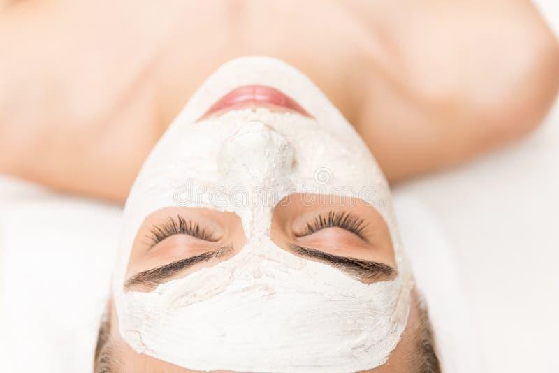 donna che si rilassa e che riceve maschera e stazione termale facciali fotografie stock