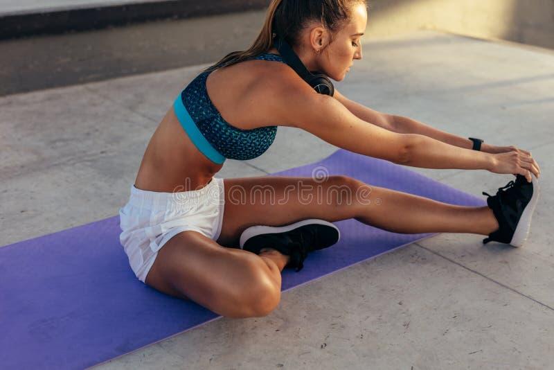 Donna che si rilassa i suoi muscoli della gamba dopo l'allenamento immagine stock