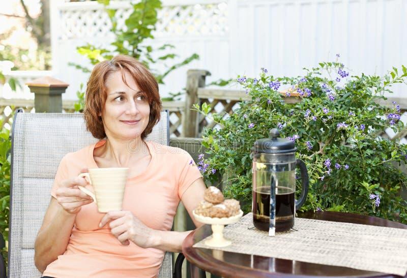 Donna che si rilassa nel cortile fotografia stock libera da diritti