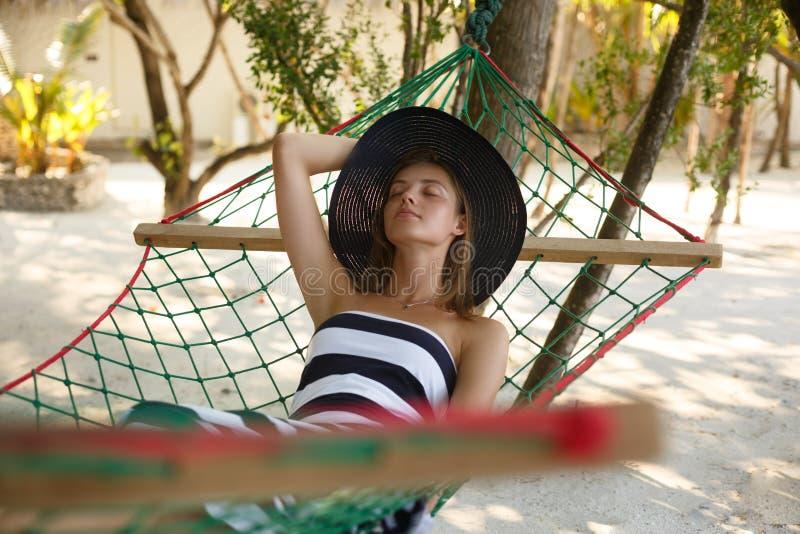 Donna che si rilassa nell'amaca sulla spiaggia tropicale nell'ombra, giorno soleggiato caldo fotografie stock