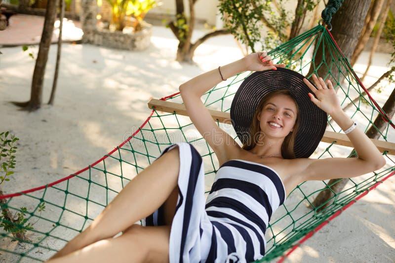 Donna che si rilassa nell'amaca sulla spiaggia tropicale nell'ombra, giorno soleggiato caldo La ragazza guarda alla macchina foto fotografia stock