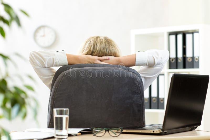 Donna che si rilassa nell'ufficio che si siede indietro nella sedia fotografie stock