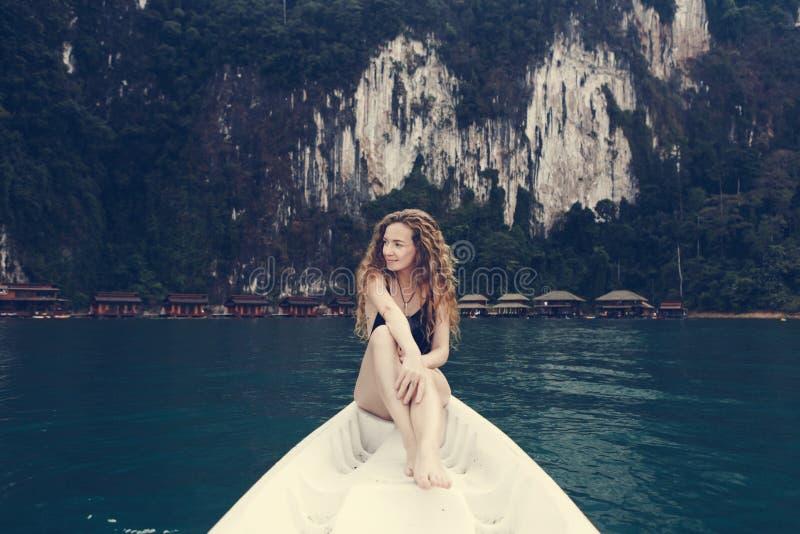 Donna che si rilassa su una canoa in un lago immagini stock libere da diritti