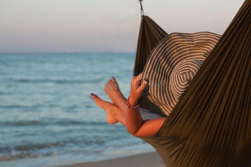 Donna che si rilassa sull'amaca con il cappello che prende il sole sulla vacanza Contro lo sfondo del mare nel tramonto immagini stock