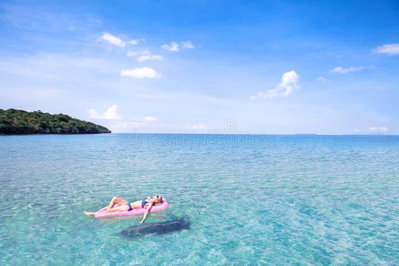 Donna che si rilassa sulla bella spiaggia con acqua del turchese, vacanza fotografia stock