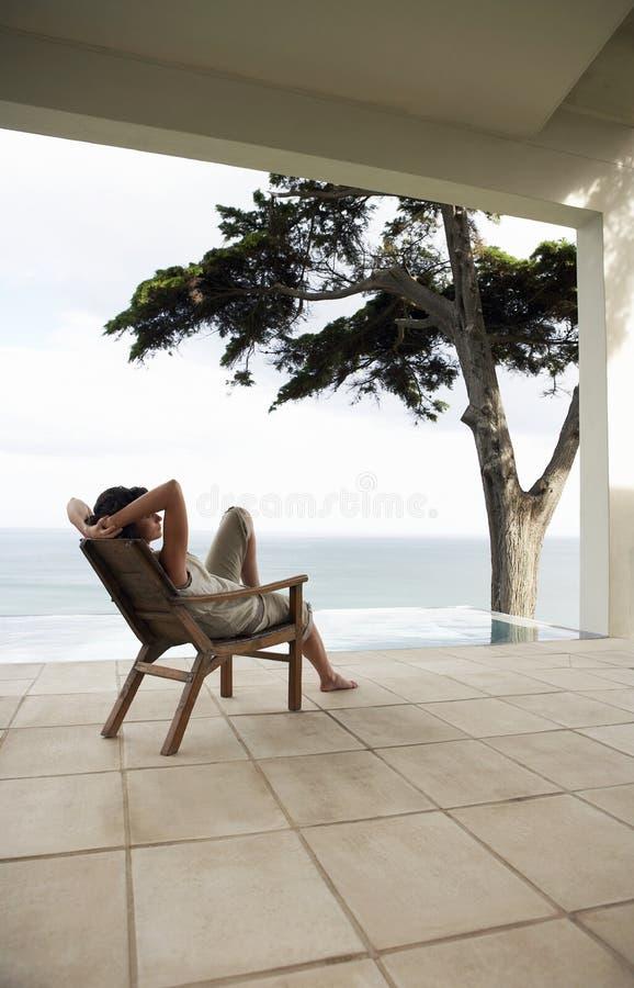 Donna che si rilassa sulla sedia di salotto dallo stagno di infinito immagini stock