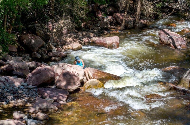 Donna che si rilassa vicino all'insenatura di Boulder in Colorado U.S.A. immagini stock