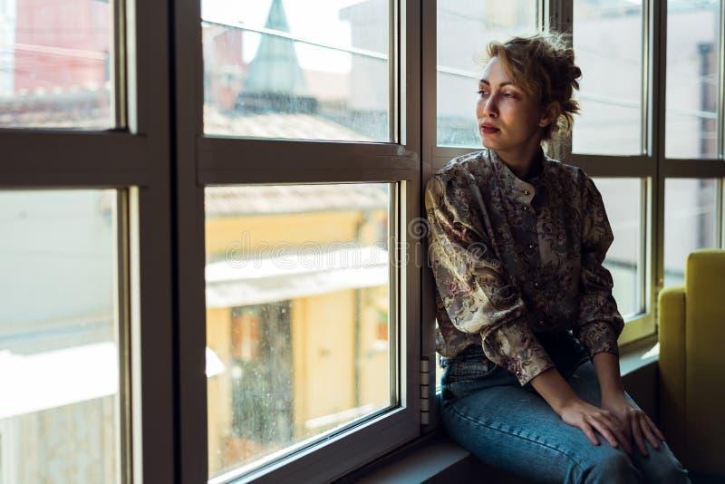 Donna che si siede accanto ad una finestra immagine stock