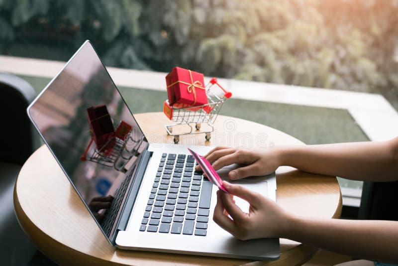 Donna che si siede al ristorante del caffè che tiene la carta di credito con il concetto online di compera fotografie stock libere da diritti