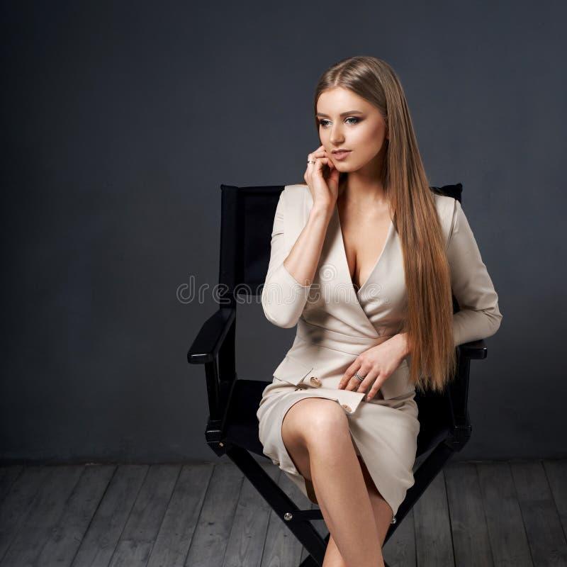 Donna che si siede all'alta sedia di direttori fotografia stock libera da diritti
