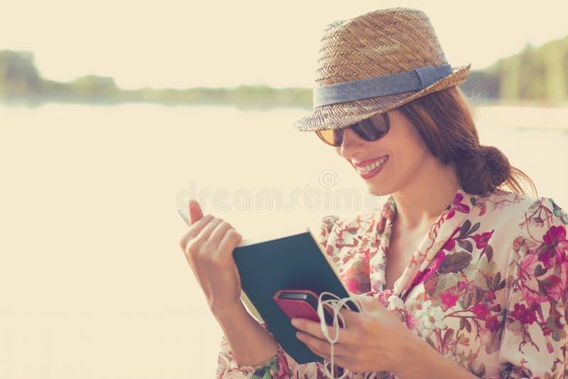 Donna che si siede all'aperto e che legge un libro fotografie stock libere da diritti