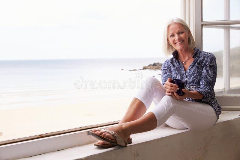 Donna che si siede alla finestra e che esamina bella vista della spiaggia immagini stock libere da diritti