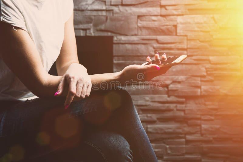 Donna che si siede alla parete e che passa in rassegna il telefono fotografie stock