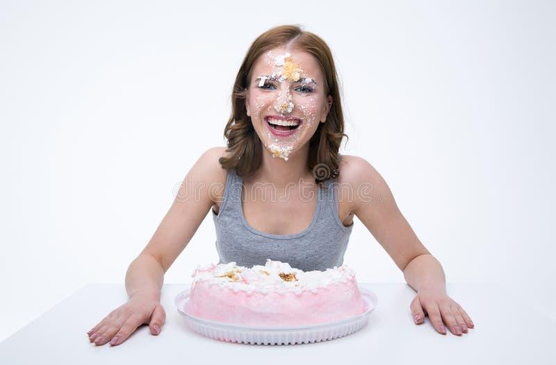 donna che si siede alla tavola con il dolce al suo fronte fotografia stock