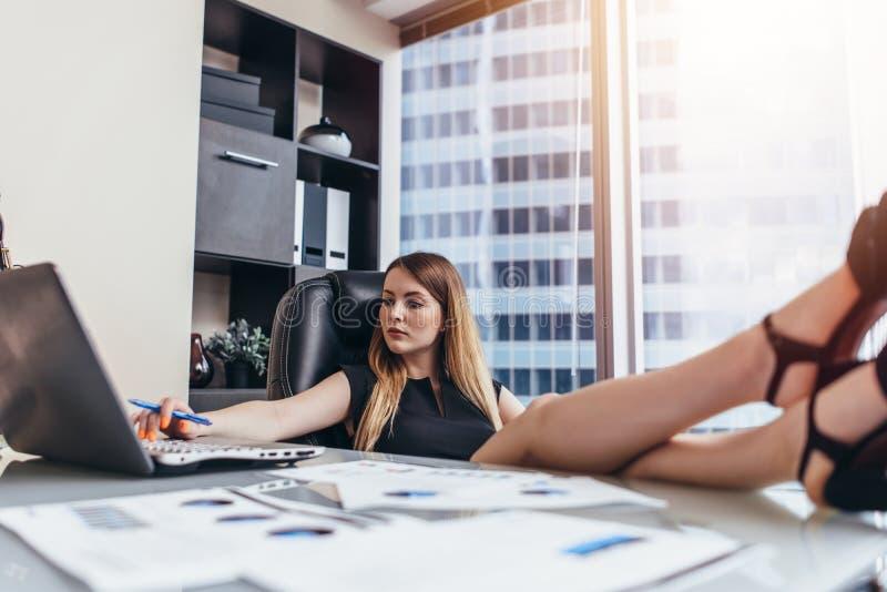 Donna che si siede allo scrittorio con le gambe sulla tavola che lavora al computer portatile che analizza le statistiche finanzi fotografie stock libere da diritti