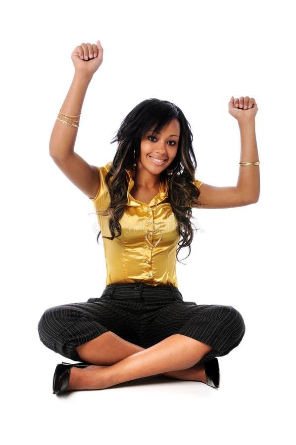 Donna che si siede con le braccia alzate immagini stock