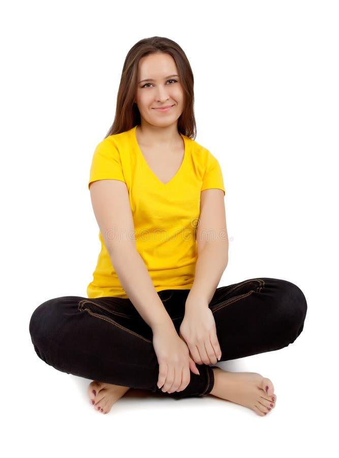 Donna che si siede con le gambe attraversate fotografia stock libera da diritti